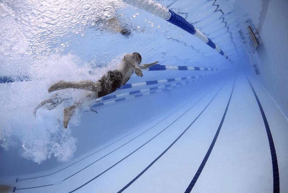Mężczyzna pływający w basenie.
