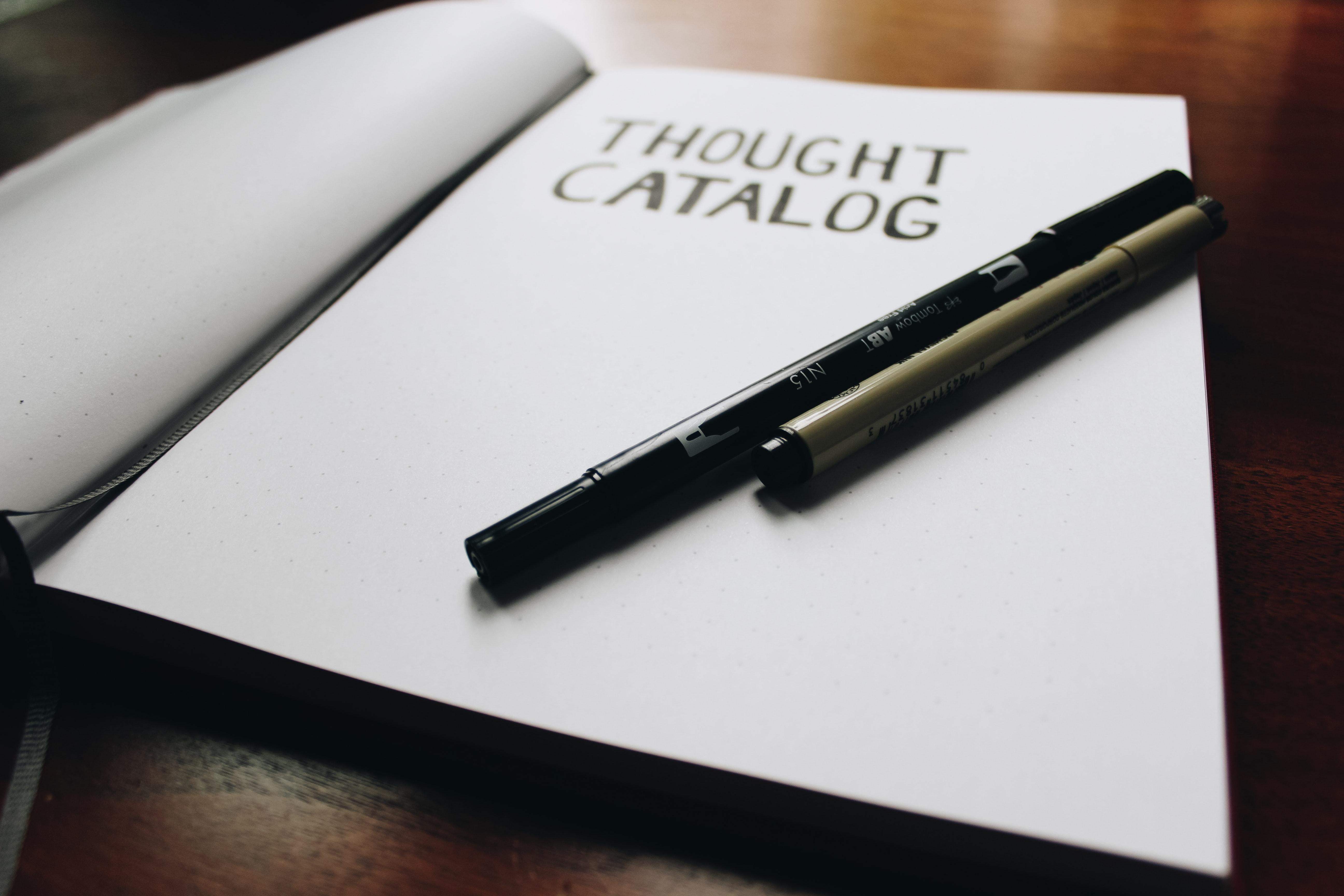 Katalog, na którym leżą długopisy.